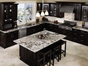 kitchen with dark black cabinets and marble tops